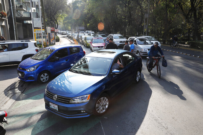 Vehicles stand in line to fill up their fuel tanks at a gas station in Mexico, City, Wednesday, Jan. 9, 2019. A fuel scarcity arose after President Andres Manuel Lopez Obrador decided to close government pipelines riddled with illegal fuel taps drilled by thieves, and instead deliver gas and diesel by tanker trucks. (AP Photo/Marco Ugarte)