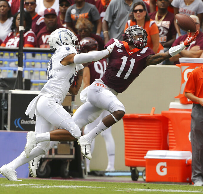 Tech receiver Tré Turner (11) reaches for a pass from quarterback Ryan Willis in front of Old Dominion defender Kaleb Ford-Dement (22) in the first half of an NCAA college football game  in Blacksburg Va,. Saturday, Sept. 7, 2019. (Matt Gentry/The Roanoke Times via AP)