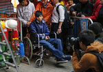 FILE - In this Dec. 5, 2014, file, photo, student leader Joshua Wong attends a news conference as he sits on a wheel chair during a hunger strike at the occupied area outside government headquarters in Hong Kong. Overseas, Joshua Wong has emerged as a prominent face of Hong Kong's months-long protests for full democracy. At home, he is just another protester. (AP Photo/Kin Cheung, File)