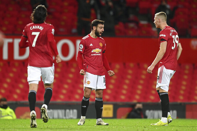 Manchester United's Bruno Fernandes, centre, celebrates after scoring his side's second goal during an English Premier League soccer match between Manchester United and Everton at the Old Trafford stadium in Manchester, England, Saturday Feb. 6, 2021. (Michael Regan/Pool via AP)