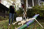 Carol McCarthy poses next to pirate-themed Halloween decorations reminding people to mask up while trick-or-treating during the COVID-19 pandemic, Monday, Oct. 26, 2020, in Palmyra, N.J. (AP Photo/Michael Perez)