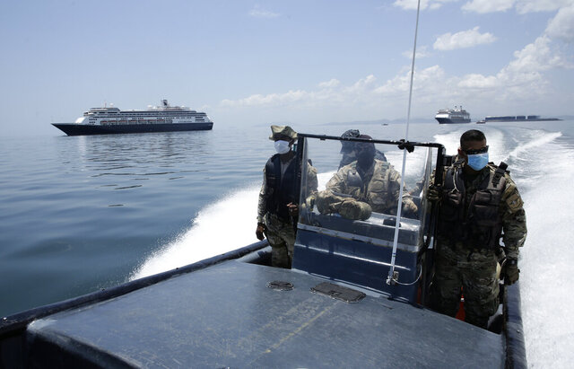 Panamanian Navy Police navigate near the anchored Zaandam cruise ship, carrying some guests with flu-like symptoms, after it arrived to the bay of Panama City, Friday, March 27, 2020, amid the worldwide spread of the new coronavirus. Health authorities are expected to board the ship to test passengers and decide whether it can cross the Panama Canal. (AP Photo/Arnulfo Franco)