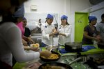 Volunteers cook donated food that would otherwise spoil due to lack of refrigeration during a blackout at Hachebistro restaurant in Caracas, Venezuela, Monday, March 11, 2019. The restaurant lent its kitchen to make