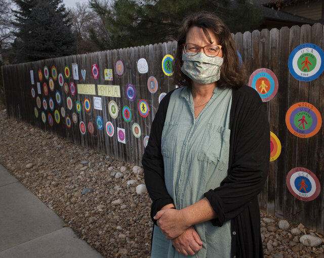 Sara Steen stands in front of the COVID-19 memorial honoring the Larimer County residents who have died from the virus as of early October in Fort Collins, Colo., on Wednesday, Nov. 18, 2020. After the emblems on the memorial were vandalized, a neighborhood-wide effort restored the memorial in less than two weeks. (Bethany Baker/The Coloradoan via AP)