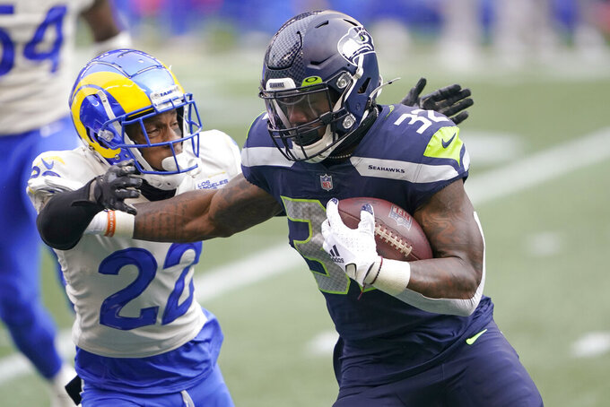 Seattle Seahawks running back Chris Carson (32) carries as Los Angeles Rams cornerback Troy Hill defends during the first half of an NFL wild-card playoff football game, Saturday, Jan. 9, 2021, in Seattle. (AP Photo/Ted S. Warren)
