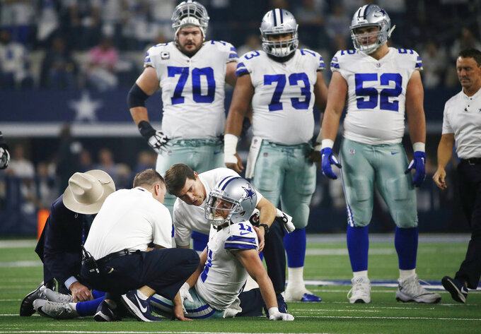 Dallas Cowboys wide receiver Cole Beasley (11) is checked on by staff after suffering an unknown injury on a pass play in the first half of the NFC wild-card NFL football game against the Seattle Seahawks, in Arlington, Texas, Saturday, Jan. 5, 2019. Beasley returned to play later in the quarter. (AP Photo/Ron Jenkins)