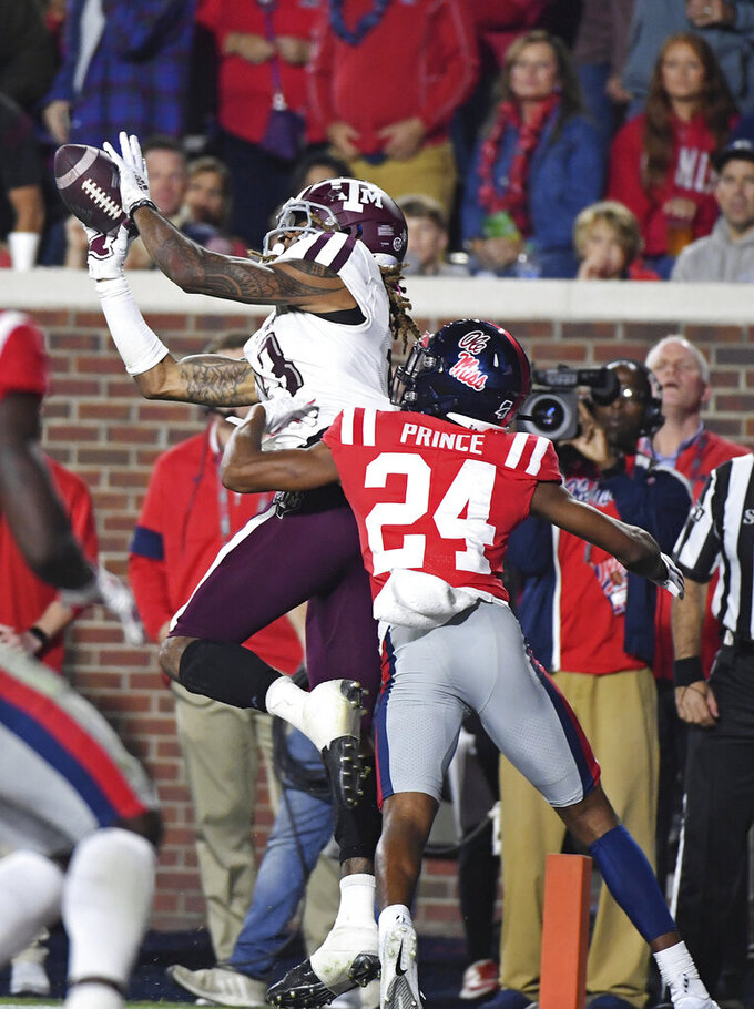 Texas A&M wide receiver Kendrick Rogers (13) catches a touchdown pass over Mississippi defensive back Deantre Prince (24) during the first half of an NCAA college football game in Oxford, Miss., Saturday, Oct. 19, 2019. (AP Photo/Thomas Graning)