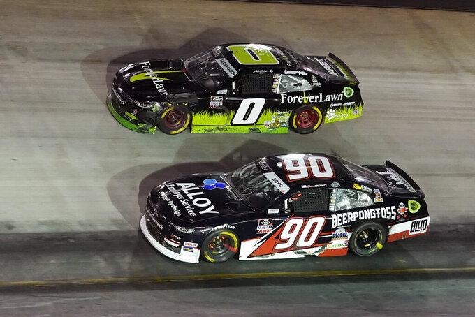 Spencer Boyd (90) and Jeffrey Earnhardt (0) drive through a turn during a NASCAR Xfinity Series auto race at Bristol Motor Speedway Friday, Sept. 17, 2021, in Bristol, Tenn. (AP Photo/Mark Humphrey)