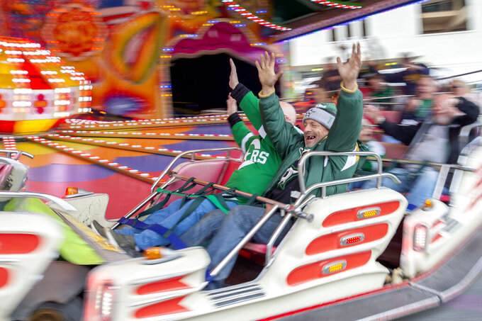 Dallas Stars fans ride carnival rides in the midway outside the Cotton Bowl before the NHL Winter Classic hockey game between the Dallas Stars and the Nashville Predators, Wednesday, Jan. 1, 2020, in Dallas. (AP Photo/Jeffrey McWhorter)