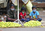 An Indian woman selling lemons sits with her children wearing face masks as a precaution against the coronavirus as they wait for buyers in Bengaluru, India, Sunday, Oct. 11, 2020. India's confirmed coronavirus toll crossed 7 million on Sunday with a number of new cases dipping in recent weeks, even as health experts warn of mask and distancing fatigue setting in. (AP Photo/Aijaz Rahi)