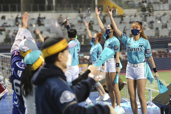Cheerleaders wearing face masks as a precaution against the coronavirus perform during Game 6 of the Korean Series, the Korea Baseball Organization's championship round, between Doosan Bears and NC Dinos at Gocheok Sky Dome in Seoul, South Korea, Tuesday, Nov. 24, 2020. Authorities in the South Korean capital on Monday announced a tightening of social distancing regulations, including shutting nightclubs, limiting service hours at restaurants and reducing public transportation. (AP Photo/Ahn Young-joon)