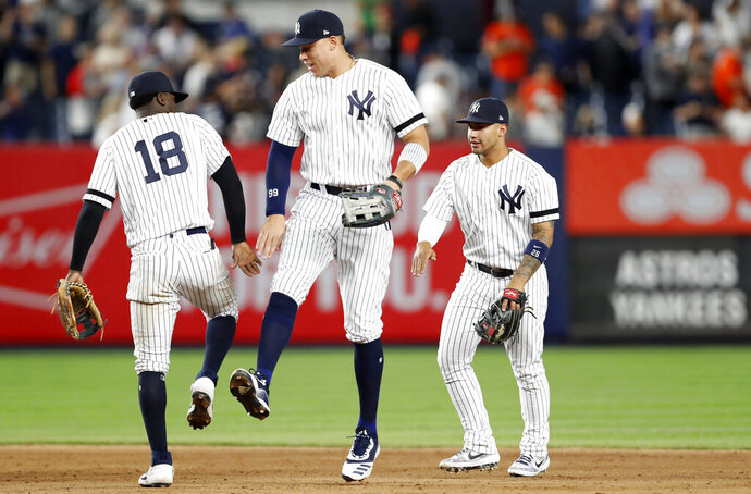 New York Yankees shortstop Didi Gregorius (18) celebrates with right fielder Aaron Judge, center, and second baseman Gleyber Torres after the Yankees defeated the Houston Astros 4-1 in a baseball game Friday, June 21, 2019, in New York. (AP Photo/Kathy Willens)