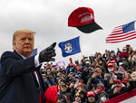 President Donald Trump tosses a cap during a campaign stop in Waterford Township, Mich., Friday Oct. 30, 2020. (Nicole Hester/Ann Arbor News via AP)
