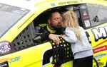 FILE - In this June 9, 2019, file photo, Paul Menard receives a kiss from his daughter Remi before the NASCAR cup series auto race at Michigan International Speedway, in Brooklyn, Mich. Menard has decided to walk away from NASCAR's top level after more than 460 races and Wood Brothers Racing is replacing him with Matt DiBenedetto in the iconic No. 21 Ford next season. After spending 16 years in the Cup Series, Menard said Tuesday, Sept. 10, 2019, he wants to step back from full-time racing to spend more time with his family. (AP Photo/Carlos Osorio, File)