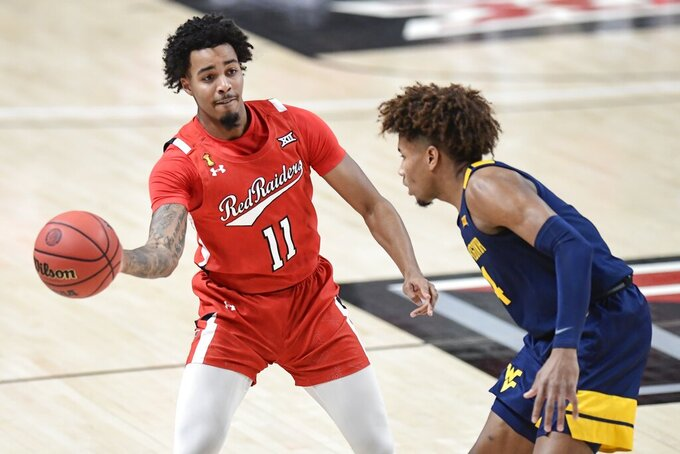 Texas Tech's Kyler Edwards (11) passes the ball during the first half of an NCAA college basketball game against West Virginia in Lubbock, Texas, Tuesday, Feb. 9, 2021. (AP Photo/Justin Rex)