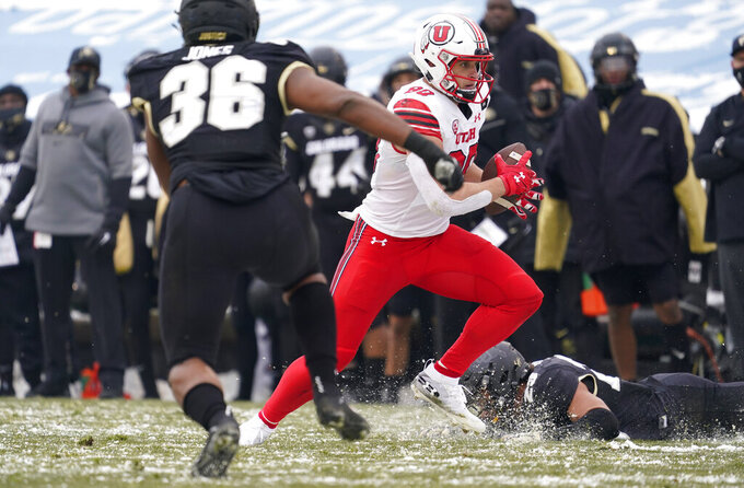 Utah tight end Brant Kuithe, center, breaks free from Colorado safety Isaiah Lewis, back, as linebacker Akil Jones comes in for the tackle in the second half of an NCAA college football game Saturday, Dec. 12, 2020, in Boulder, Colo. Utah won 38-21. (AP Photo/David Zalubowski)