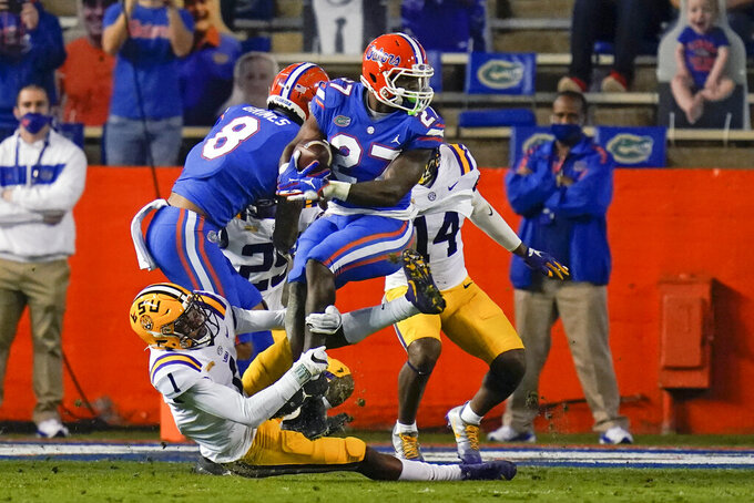 LSU cornerback Eli Ricks (1) stops a run by Florida running back Dameon Pierce, center, during the first half of an NCAA college football game Saturday, Dec. 12, 2020, in Gainesville, Fla. (AP Photo/John Raoux)