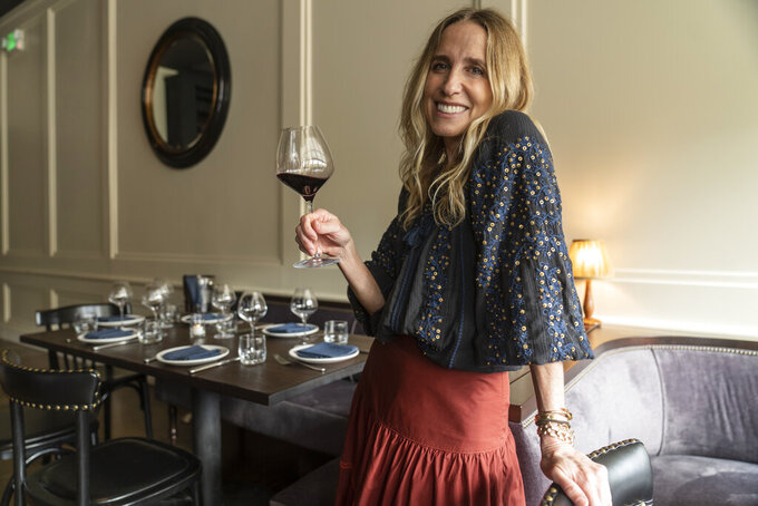 In this Saturday, June 19, 2021, photo, Caroline Styne, owner and wine director at The Lucques Group, smiles with a glass of wine at the A.O.C. Brentwood restaurant in Los Angeles. Styne has turned away dozens of customers at the company's A.O.C. West Hollywood restaurant because she doesn't have the staff to serve them, leaving seats empty. (AP Photo/Damian Dovarganes)