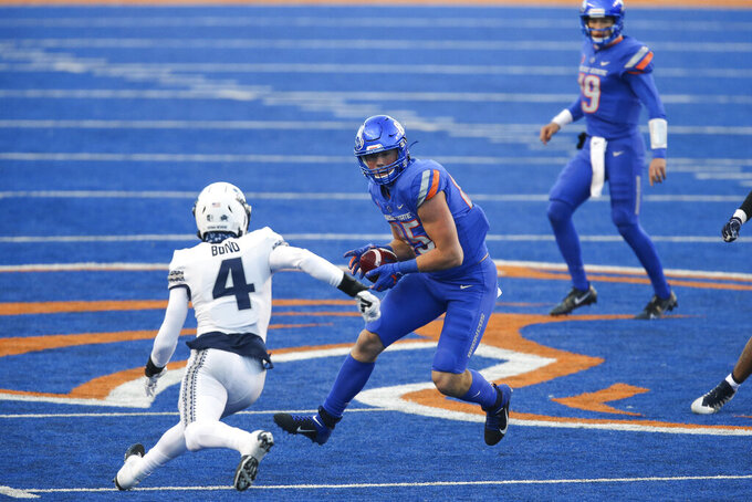 Boise State tight end John Bates (85) turns up field after a catch as Utah State safety Shaq Bond (4) closes in during the first half in an NCAA college football game Saturday, Oct. 24, 2020, in Boise, Idaho. Boise State won 42-13. (AP Photo/Steve Conner)