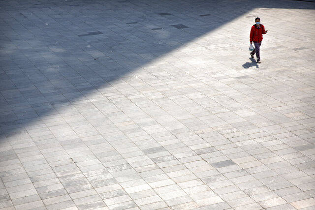 A man wears a face mask to help stop the spread of the coronavirus as he walks across an empty plaza in Beijing, Tuesday, April 7, 2020. China on Tuesday reported no new deaths from the coronavirus over the past 24 hours and just a few dozen new cases, all from people who returned from overseas. (AP Photo/Mark Schiefelbein)
