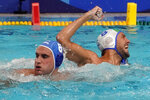 Italy's Gonzalo Echenique, right, celebrates after scoring past Greece's Stylianos Argyropoulos Kanakakis, left, during a preliminary round men's water polo match at the 2020 Summer Olympics, Tuesday, July 27, 2021, in Tokyo, Japan. (AP Photo/Mark Humphrey)