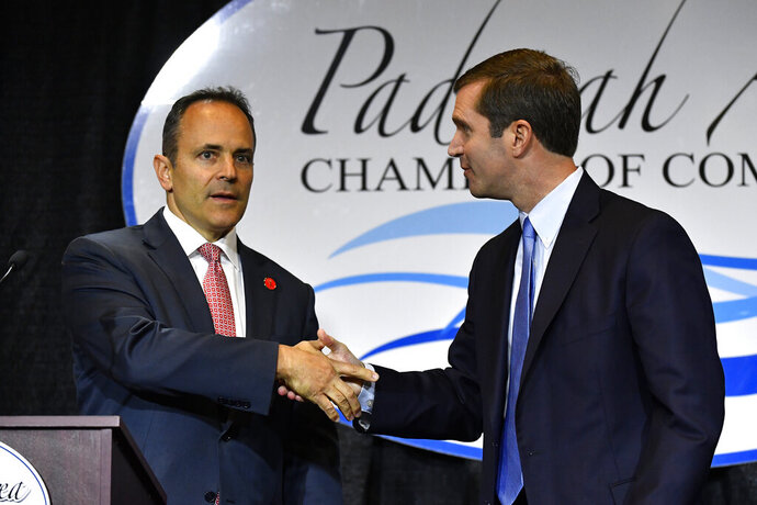 FILE - In this Thursday, Oct. 3, 2019 file photo, Kentucky Governor and Republican candidate Matt Bevin, left, shakes hands with Attorney General and Democratic candidate Andy Beshear before the start of a gubernatorial debate in Paducah, Ky. Beshear offered a vigorous defense of Kentucky's Medicaid expansion, warning Monday, Oct. 21, 2019 that health care policy is at stake when voters choose between him and Republican Gov. Matt Bevin. (AP Photo/Timothy D. Easley, File)