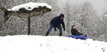Dana Terry gives son Logan, 6, a push from the top of the hill while sledding at Fish Park in Poulsbo, Wash., Monday, Jan. 13, 2020. (Meegan M. Reid/Kitsap Sun via AP)