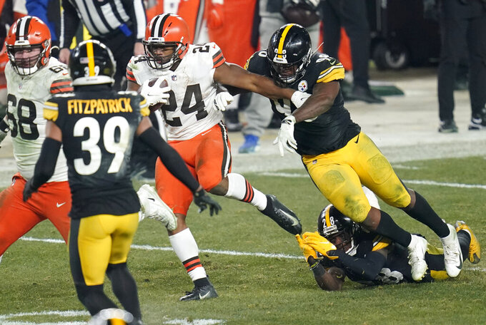 Cleveland Browns running back Nick Chubb (24) breaks the tackles of Pittsburgh Steelers inside linebacker Vince Williams (98) and Mike Hilton (28) to score during the second half of an NFL wild-card playoff football game, Sunday, Jan. 10, 2021, in Pittsburgh. (AP Photo/Keith Srakocic)