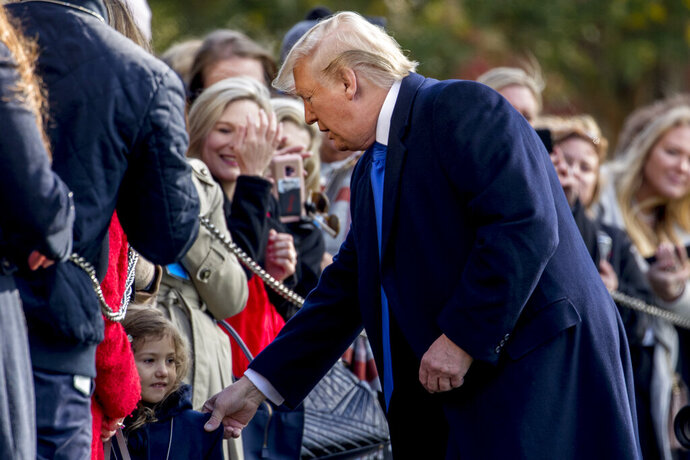 President Donald Trump pulls a girl out of the audience for a photograph on the South Lawn of the White House in Washington, Friday, Nov. 8, 2019, before boarding Marine One for a short trip to Andrews Air Force Base, Md. and then on to Georgia to meet with supporters. (AP Photo/Andrew Harnik)