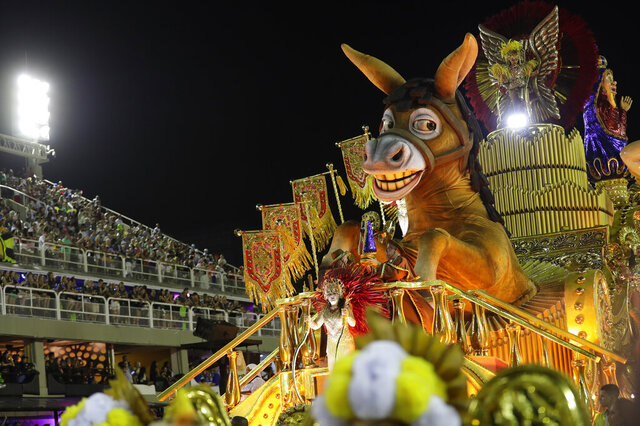 Performers from the Sao Clemente samba school parade on a float during Carnival celebrations at the Sambadrome in Rio de Janeiro, Brazil, Monday, Feb. 24, 2020. (AP Photo/Silvia Izquierdo)
