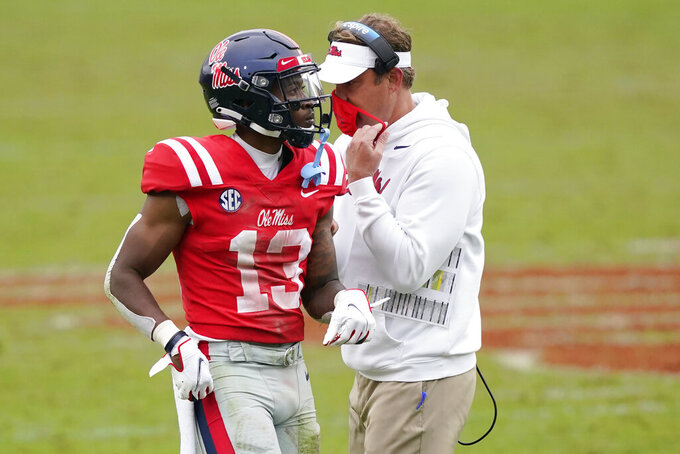 Mississippi head coach Lane Kiffin, right, confers with Mississippi wide receiver Braylon Sanders (13) during the second half of an NCAA college football game against Auburn in Oxford, Miss., Saturday Oct. 24, 2020. (AP Photo/Rogelio V. Solis)
