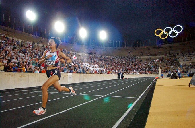 FILE - In this Aug. 22, 2004, file photo, Japan's Mizuki Noguchi takes the final lap inside the Panathinaiko Stadium as she wins the gold medal in the women's marathon in the 2004 Olympic Games in Athens. (AP Photo/Richard Drew, File)