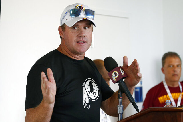 FILE - In this July 24, 2019, file photo, then-Washington Redskins head football coach Jay Gruden gestures during a news conference at the Redskins NFL training camp in Charlottesville, Va. The Jacksonville Jaguars have hired former Washington coach Jay Gruden as their offensive coordinator. Gruden signed his contract Wednesday, Jan. 22, 2020, and replaces John DeFilippo, who was fired earlier this month after just one season. (AP Photo/Steve Helber, File)