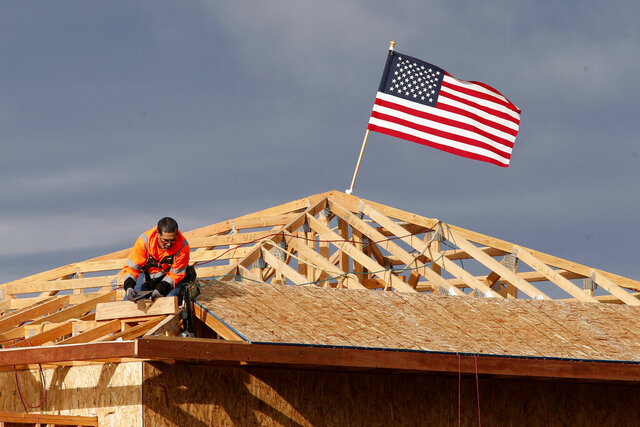 FILE — In this March 31, 2020 file photo the American flag flutters in the wind as work is done on the roof of a building under construction in Sacramento, Calif. On Friday April 17, 2020, the California Employment Development Department announced the state's unemployment rate jumped to 5.3% in March, up from 3.9% the previous month. Construction job losses made up 11.6% of the decline. (AP Photo/Rich Pedroncelli, File)