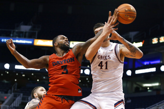 Dayton guard Trey Landers (3) knocks the ball away from Saint Mary's center Aaron Menzies (41) during the first half of an NCAA college basketball game, Sunday, Dec. 8, 2019, in Phoenix. (AP Photo/Ralph Freso)