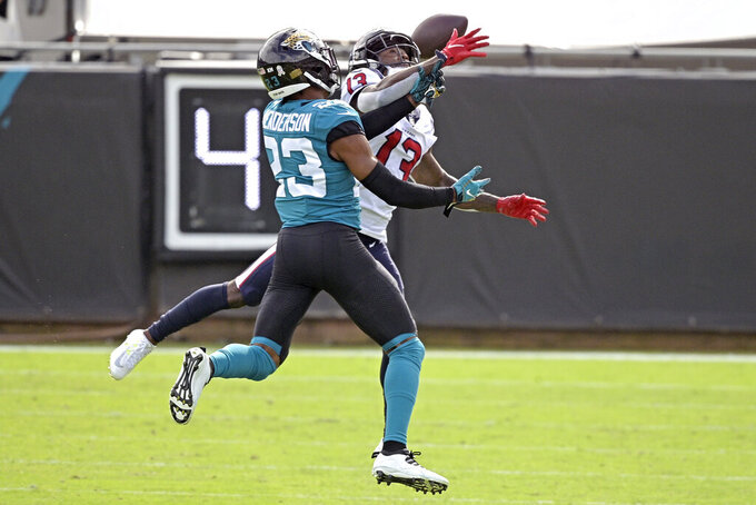 Jacksonville Jaguars cornerback CJ Henderson, left, breaks up a pass intended for Houston Texans wide receiver Brandin Cooks (13) during the first half of an NFL football game, Sunday, Nov. 8, 2020, in Jacksonville, Fla. (AP Photo/Phelan M. Ebenhack)