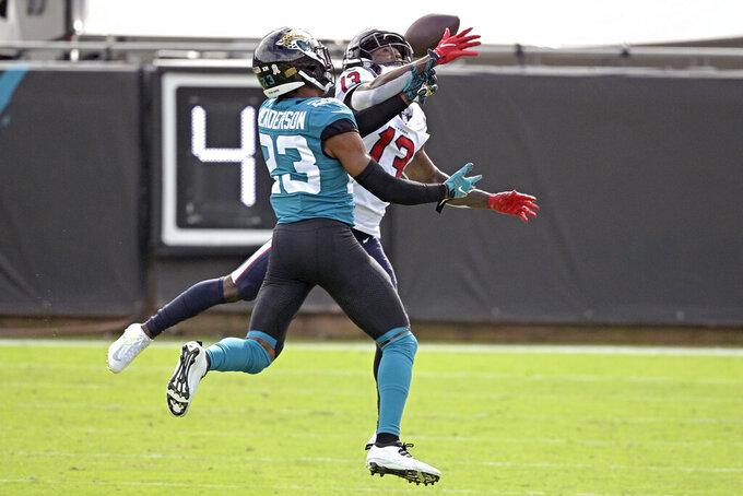 Jacksonville Jaguars cornerback CJ Henderson, left, breaks up a pass intended for Houston Texans wide receiver Brandin Cooks (13) during the first half of an NFL football game, Sunday, Nov. 8, 2020, in Jacksonville, Fla. (AP Photo/Phelan M. Ebenhack)