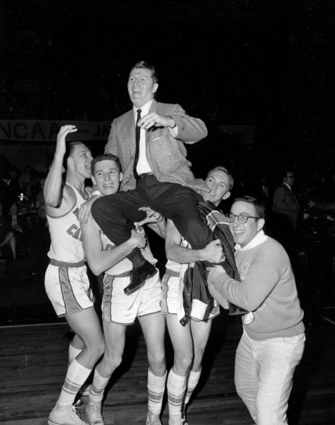 FILE - In this March 23, 1957, file photo, North Carolina players hoist head coach Frank McGuire as they celebrate their 54-53 victory over Kansas in the NCAA college basketball championship final in Kansas City, Mo. (AP Photo/William P. Straeter, File)