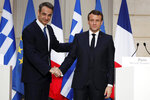French President Emmanuel Macron, right, and Greek Prime Minister Kyriakos Mitsotakis shake hands during a joint press conference at the Elysee Palace in Paris, Wednesday Jan. 29, 2020. (Benoit Tessier/Pool via AP)