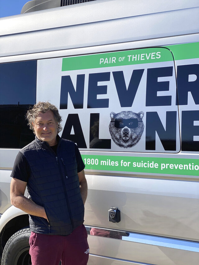 This photo provided by Pair of Thieves shows Doug Peterson posed recently in Pacific City, Ore., next to the camper van that will accompany him on a nearly 1,500-mile bike ride to raise awareness for National Suicide Prevention Month. It was January 2015 that 17-year-old Page Peterson, the carefree Oregon boy who pitched on the baseball field and tore down the slopes on his snowboard, took his own life. He was among more than 2,000 teenagers his age that would commit suicide in that year alone, a number that is both staggering and heartbreaking. Now, his father Doug Peterson is riding his bike from the Canadian border to the Mexican border during the month of September, raising money with the support of apparel company Pair of Thieves and awareness for National Suicide Prevention Month. (Alan Stuart/Pair of Thieves via AP)