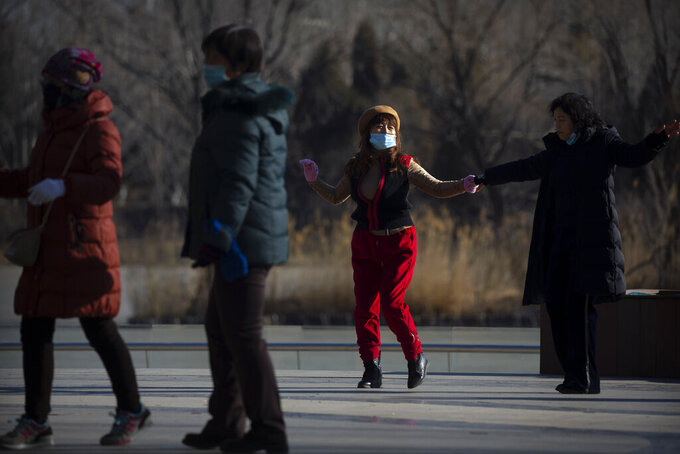 People wearing face masks to curb the spread of the coronavirus dance at a public park in Beijing, Tuesday, Jan. 5, 2021. China has designated parts of Hebei province near Beijing as a coronavirus high danger zone after 14 new cases of COVID-19 were found. (AP Photo/Mark Schiefelbein)