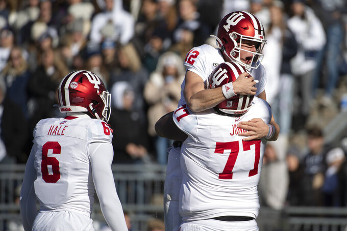 Indiana quarterback Peyton Ramsey (12) celebrates with offensive lineman Caleb Jones (77) after scoring a touchdown during the first quarter of NCAA college football game against Penn State in State College, Pa., on Saturday, Nov.16, 2019. (AP Photo/Barry Reeger)