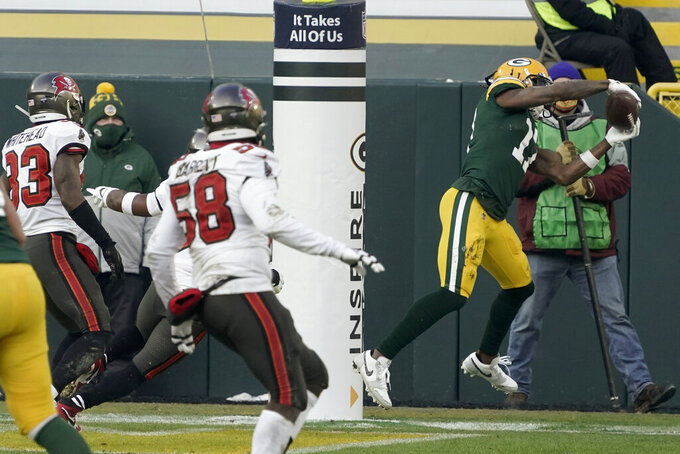 Green Bay Packers' Davante Adams (17) catches a pass out of bounds in the end zone against the Tampa Bay Buccaneers during the first half of the NFC championship NFL football game in Green Bay, Wis., Sunday, Jan. 24, 2021. (AP Photo/Morry Gash)