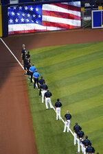 Miami Marlins players stand during the singing of the national anthem before a baseball game against the Atlanta Braves, Friday, Aug. 14, 2020, in Miami. (AP Photo/Wilfredo Lee)