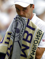 Spain's Roberto Bautista Agut wipes his face with a towel as he plays Serbia's Novak Djokovic in a Men's singles semifinal match on day eleven of the Wimbledon Tennis Championships in London, Friday, July 12, 2019. (AP Photo/Kirsty Wigglesworth)