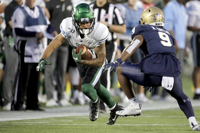Tulane wide receiver Jacob Robertson Jr. runs with the ball against Navy cornerback Daniel Taylor (9) during the second half of an NCAA college football game, Saturday, Oct. 26, 2019, in Annapolis. Navy won 41-38. (AP Photo/Julio Cortez)