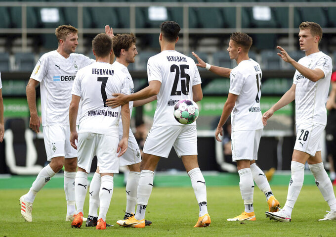 Moenchengladbach's scorer Ramy Bensebaini, center, and his teammates celebrate their side's fourth goal during the German Soccer Cup first round match between Borussia Moenchengladbach and FC Oberneuland in  Moenchengladbach, Germany, Saturday, Sept. 12, 2020. (Bernd Thissen/dpa via AP)