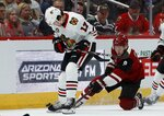 Arizona Coyotes center Clayton Keller (9) pokes the puck away from Chicago Blackhawks center Dylan Strome (17) during the first period of an NHL hockey game Tuesday, March 26, 2019, in Glendale, Ariz. (AP Photo/Ross D. Franklin)