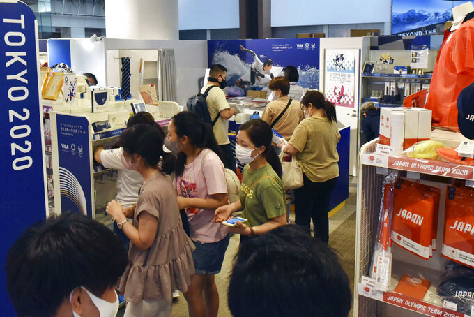 """People visit a Tokyo Olympics official goods store in Tokyo on July 27, 2021.When the Tokyo Olympics began during a worsening pandemic, the majority of the host nation was in opposition, with Emperor Naruhito dropping the word """"celebrating"""" from his opening declaration of welcome. But once the Games got underway and local media switched to covering Japanese athletes' """"medal rush,"""" many were won over.  (Kyodo News via AP)"""