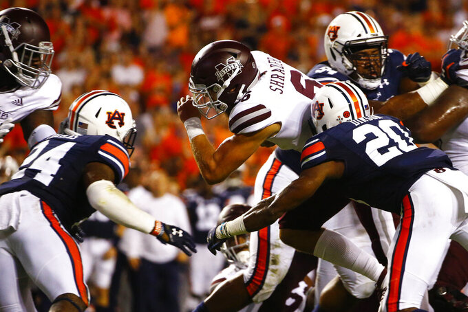 Mississippi State quarterback Garrett Shrader (6) carries the ball for a first down as Auburn defensive backs Jeremiah Dinson (20) and Daniel Thomas (24) defend during the first half of an NCAA college football game, Saturday, Sept. 28, 2019, in Auburn, Ala. (AP Photo/Butch Dill)